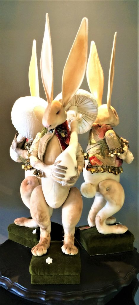 Mr Finch - three long-eared rabbits wearing exquisite handmade garments, trimmed in tiny bells and envelopes and standing on green velvet covered boxes.