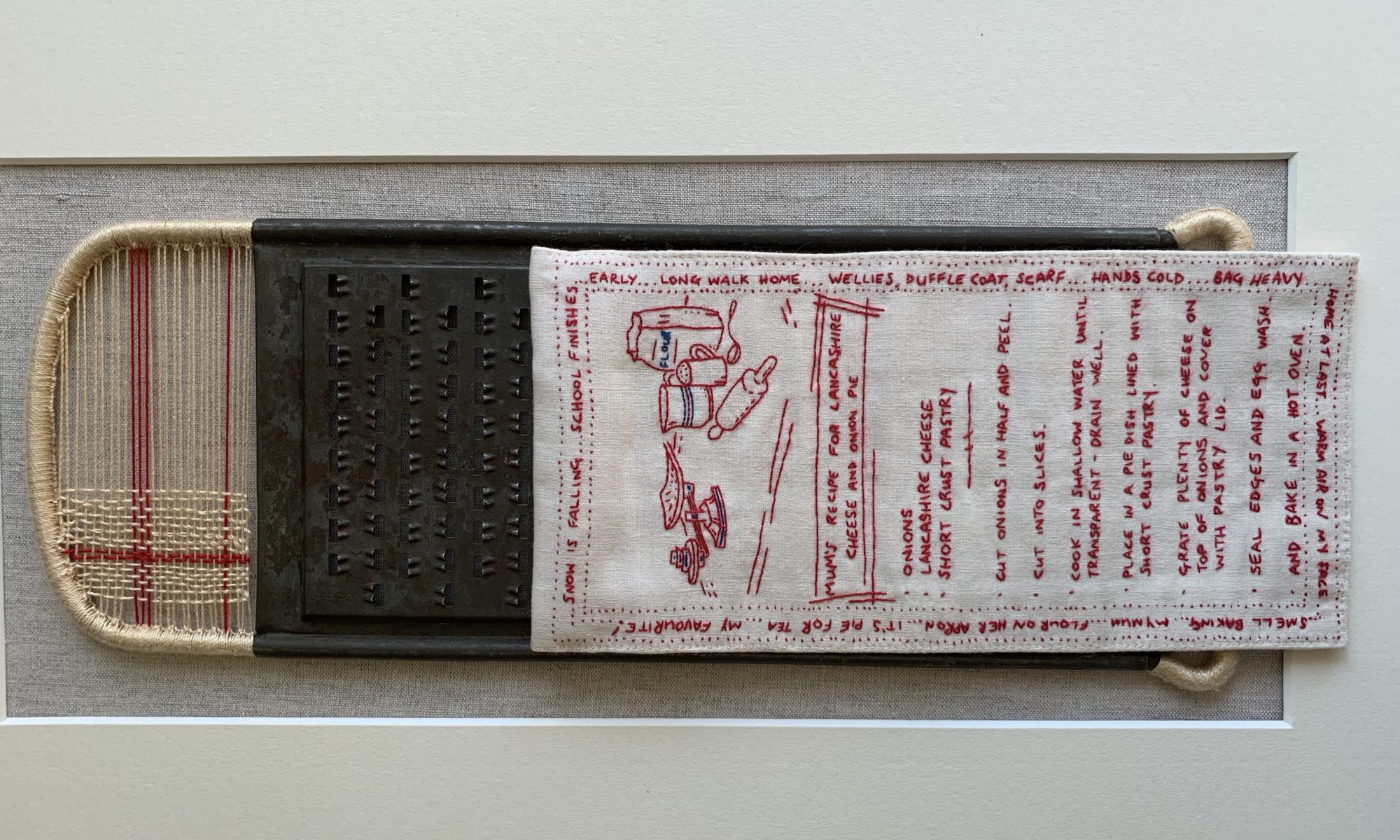 Open Door Exhibition 2020 - An embroidered textile art piece in red thread on white cloth, displayed on a cheese grater. An embroidered artwork based on my Mum's own recipe - a childhood favourite of mine.