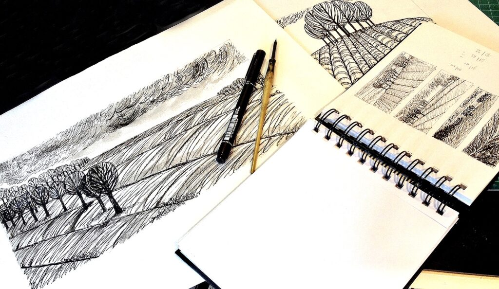 sketch books showing art and sketches in black and white of ploughed fields and trees