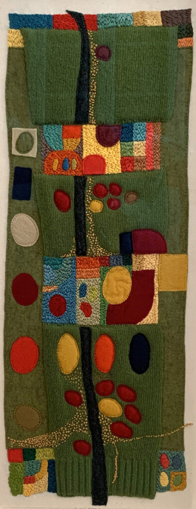 Greensleeves. image showing showing the sleeve from a green jumper embroidered in multicoloured shapes