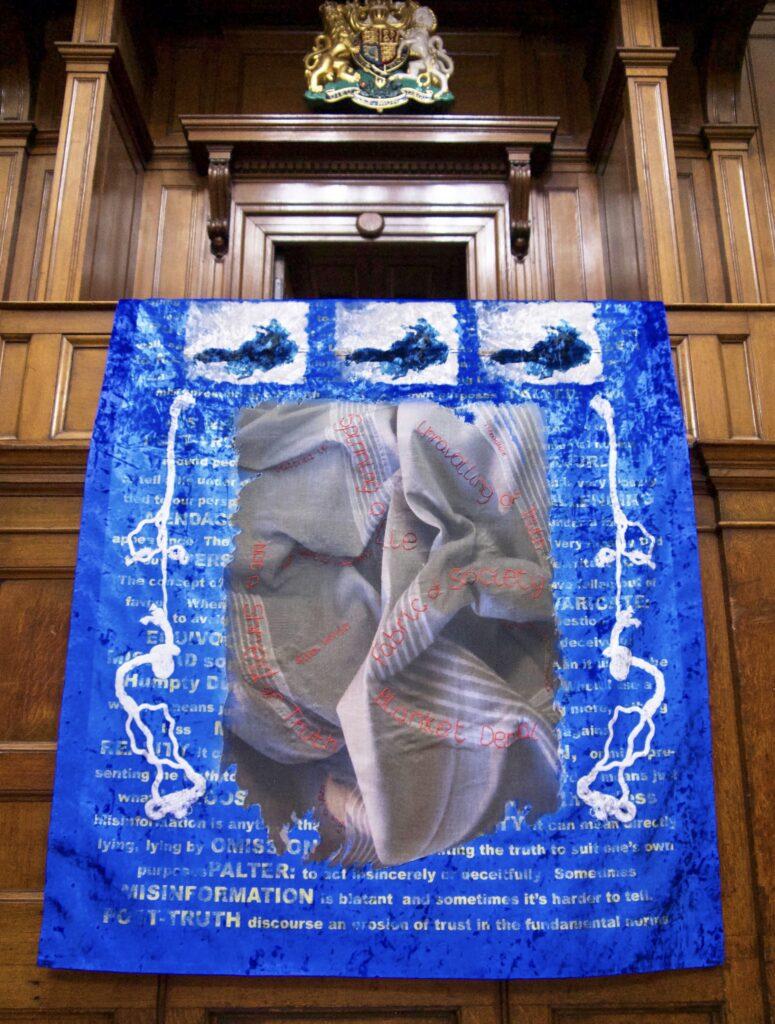 textile art, blue velvet and text about the death of Jamal Khashoggi. Art by Linda Izan.
