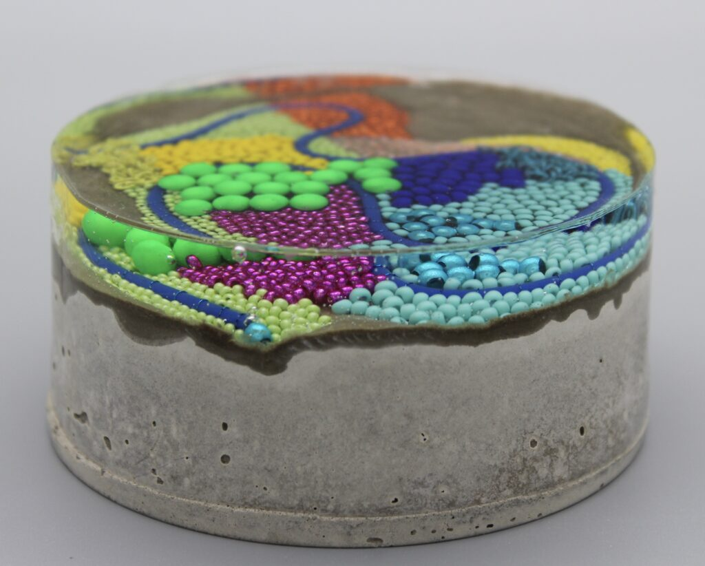 'Substratum' - beaded art set inside resin and concrete -  created by Claire Edwards