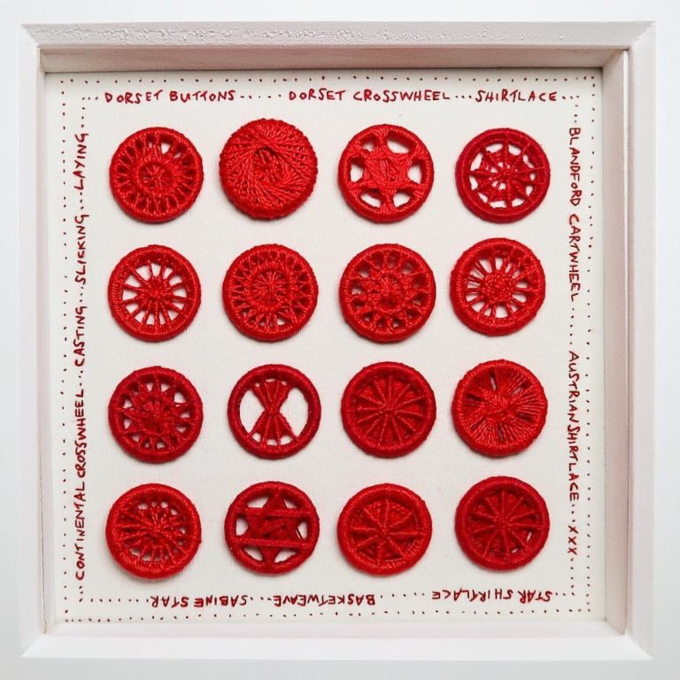 A collection of red handmade dorset buttons stitched onto a panel with hand embroidered words around the edge stating the names of the different types of dorset buttons. All made in red thread.