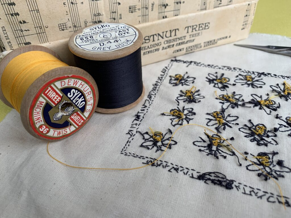 Worker Bees - Reverse of the work in progress - wooden reels of vintage threads in yellow and slate grey and the reverse of hand embroidered bees