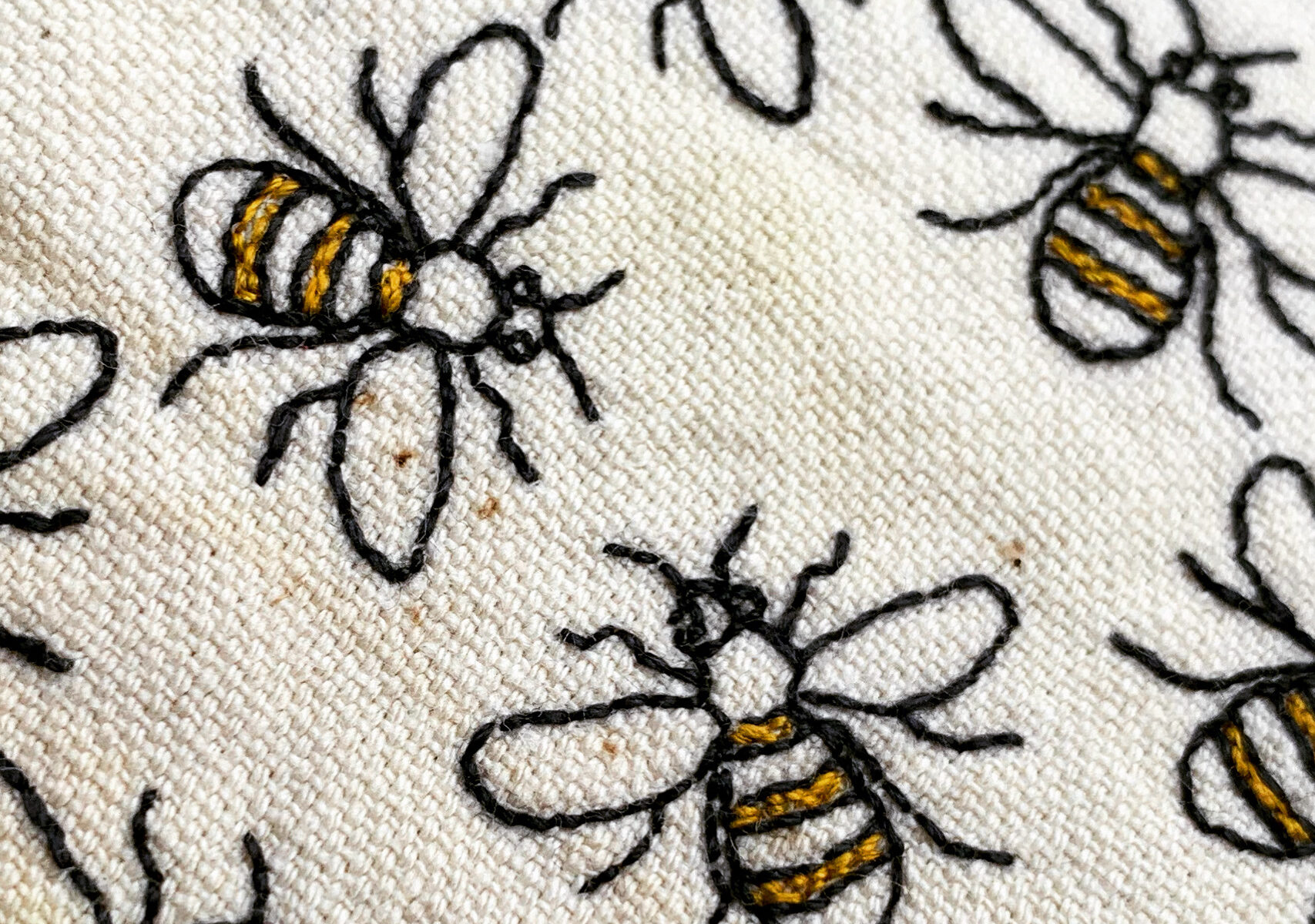 Close up of the hand embroidered bees in yellow and slate grey