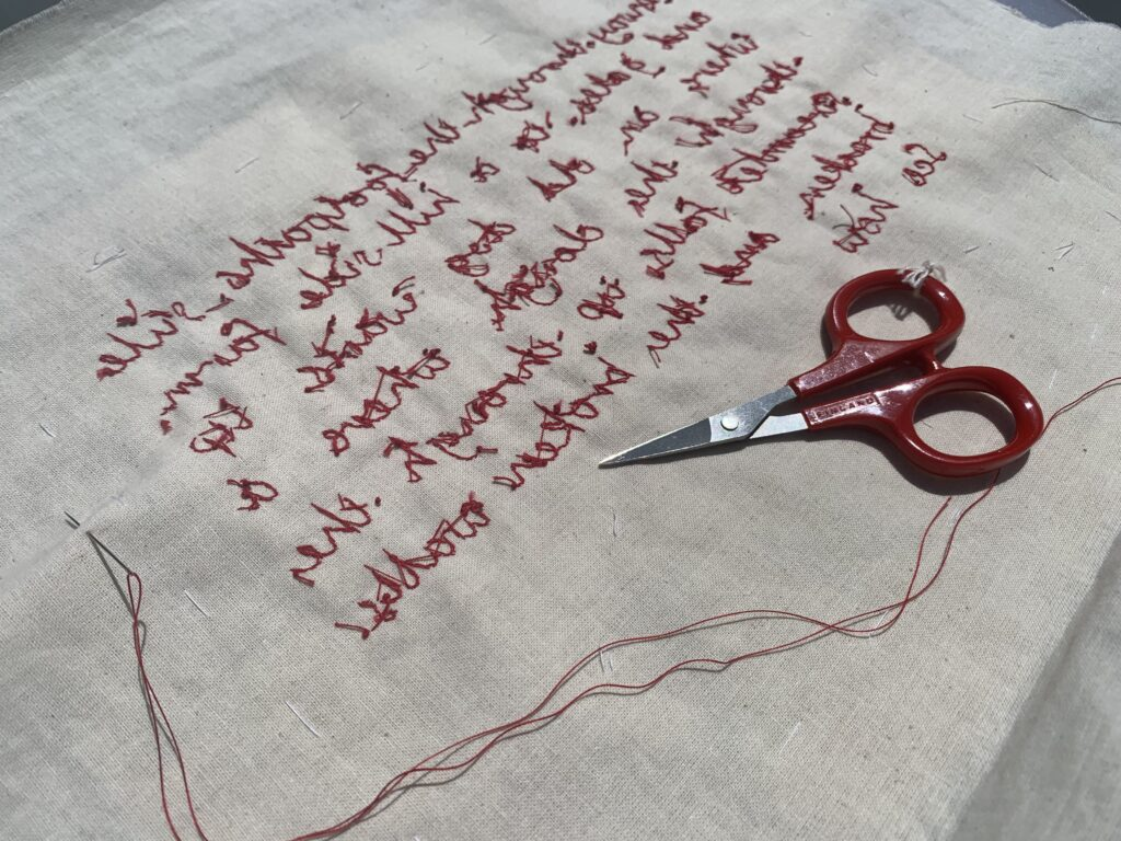 The reverse of  the work showing red thread embroidery on cloth