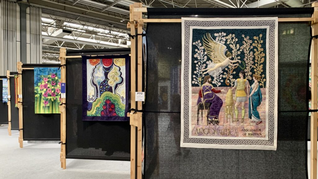 quilts hanging on quilt stands at the Festival of Quilts 2021