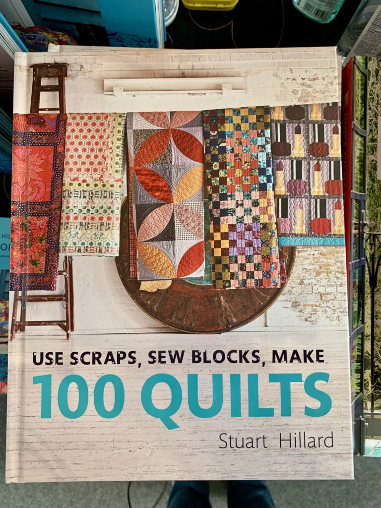 100 quilts book by Stuart Hillard with multicoloured patchwork quilts on the cover