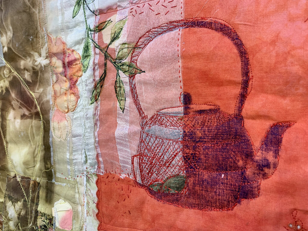 Machine embroidered kettle on a red cloth by Cas Holmes