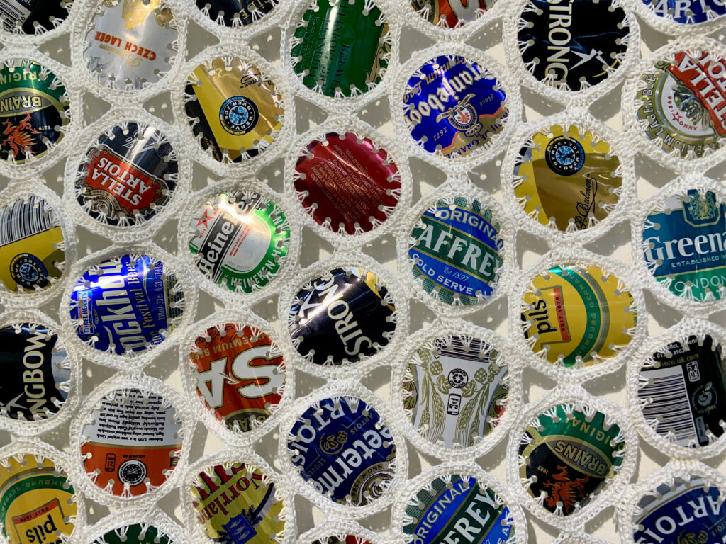 Art Textiles Made in Britain - circles of cut out beer cans crocheted together with white thread - called Keep the Homeless Warm