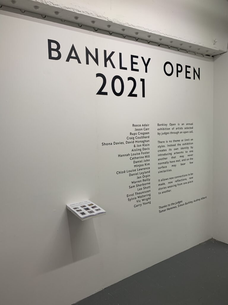 list of artists displayed on a wall inside the gallery space