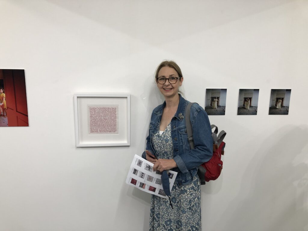 Bankley 2021 Opening Night - me standing next to my red hand embroidered artwork